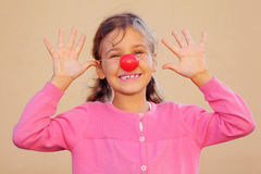 Girl with red clown nose smiles Royalty Free Stock Photos
