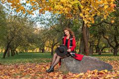A girl in a red coat and with a black hat in her hands crouched on a stone in the autumn forest royalty free stock images