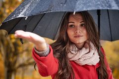 A girl in a red coat with a black umbrella Stock Image