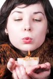 Girl in red coat blow on candle Royalty Free Stock Photos