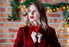 Girl in red coat at Christmas lights background. Portrait of a young girl in red coat at Christmas lights background royalty free stock photos