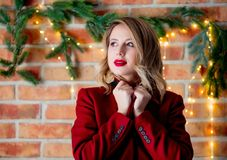 Girl in red coat at Christmas lights background. Portrait of a young girl in red coat at Christmas lights background stock photo