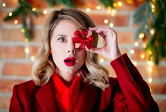 Girl in red coat with gift box at Christmas lights background. Portrait of a young girl in red coat with gift box at Christmas lights background stock photography