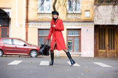 Girl in a red coat moves outdoors Royalty Free Stock Photos