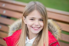 Girl in red coat sit on bench in park Royalty Free Stock Image