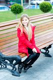 Girl in red coat sit on bench in park Royalty Free Stock Photography