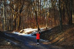 Girl in red coat was frozen in the middle of a spring forest. She's trying to warm his hands Stock Photo
