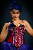 Girl in a red corset on a dark background Stock Images