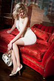 Girl on the red couch. Girl in a beige dress on the red couch Royalty Free Stock Images
