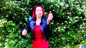 Girl with red hair dances, naughty, laughs, smiles, engaged with different subjects. Girl with red or crimson hair dances, naughty, laughs, smiles, engaged with stock video footage