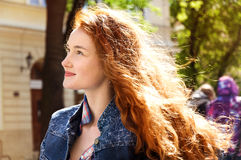 Girl with red curly hair. hair burn like fire in the sun Stock Photography