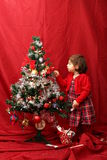 Girl in red and the decorated Christmas tree Royalty Free Stock Photo