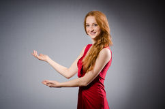 Girl in red dress against gray Stock Photo