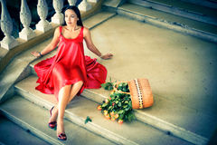 Girl in a red dress with a basket of roses Stock Photo