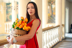 Girl in a red dress with a basket of roses Royalty Free Stock Photos