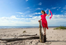 Girl in red dress  on a beach. Royalty Free Stock Photography