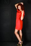 Girl in red dress black background Stock Photos