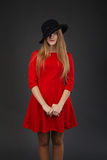 Girl in red dress and black hat. Stock Photo