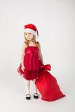The girl in a red dress with a bow in the bell Santa Claus Stock Photography