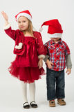 Girl in a red dress and boy in Santa Claus hat Royalty Free Stock Photo