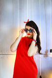 The girl in a red dress. The brunette in a red dress poses on a gold background in sunglasses Royalty Free Stock Image