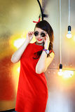 The girl in a red dress. The brunette in a red dress poses on a gold background in sunglasses Stock Photo