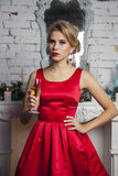 Girl in red dress with Christmas champagne. Celebration Stock Image