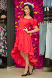 The girl in a red dress in a clothing store Stock Images