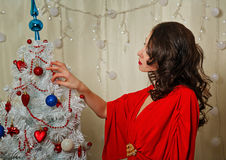 Girl in red dress corrects ornaments Christmas tree. Royalty Free Stock Photos