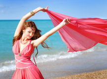 The girl in red dress dances. On beach Stock Image