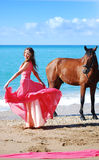 The girl in red dress dances on beach. Nearby there is horse Stock Images