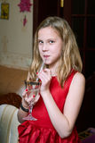 Girl in red dress drinking champagne for children Royalty Free Stock Images