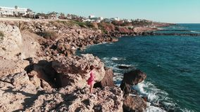 Girl in red dress flapping on wind stands on rocky cliff with hands apart with strong sea waves hitting seashore splashing and cre. Ating foam. Aerial drone view stock video