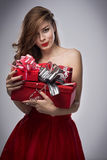 Girl in red dress with gifts Stock Images