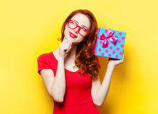 Girl in red dress with glasses and gift box Royalty Free Stock Photography