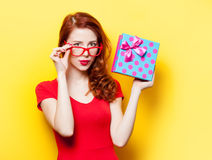 Girl in red dress with glasses and gift box Stock Image