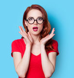 Girl in red dress with glasses. Surprised redhead girl in red dress with glasses on blue background Royalty Free Stock Image