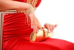 Girl in red dress with gold bag Stock Photography