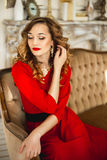 The girl in a red dress with gold costume jewelry Royalty Free Stock Photo