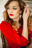 The girl in a red dress with gold costume jewelry Stock Photo