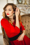 The girl in a red dress with gold costume jewelry Royalty Free Stock Photography
