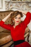 The girl in a red dress with gold costume jewelry Stock Images