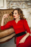 The girl in a red dress with gold costume jewelry Royalty Free Stock Photos