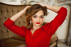 The girl in a red dress with gold costume jewelry Royalty Free Stock Image