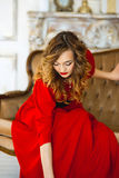 The girl in a red dress with gold costume jewelry Stock Photos