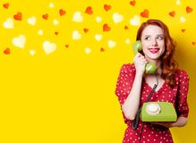 Girl in red dress with green dial phone and hearts. Smiling redhead girl in red polka dot dress with green dial phone and hearts on yellow background Stock Photography