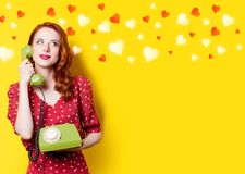 Girl in red dress with green dial phone and hearts. Smiling redhead girl in red polka dot dress with green dial phone and hearts on yellow background Royalty Free Stock Photo