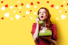 Girl in red dress with green dial phone and hearts. Surprised redhead girl in red polka dot dress with green dial phone and hearts on yellow background Stock Images