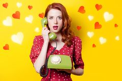 Girl in red dress with green dial phone and hearts. Surprised redhead girl in red polka dot dress with green dial phone and abstract hearts on yellow background Stock Photos