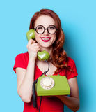 Girl in red dress with green dial phone Royalty Free Stock Photos